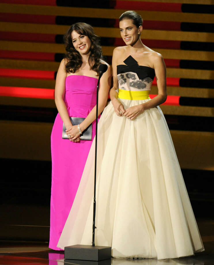 Zooey Deschanel, left, and Allison Williams present the award for outstanding writing for a comedy series at the 66th Annual Primetime Emmy Awards at the Nokia Theatre L.A. Live on Monday, Aug. 25, 2014, in Los Angeles. (Photo by Chris Pizzello/Invision/AP)