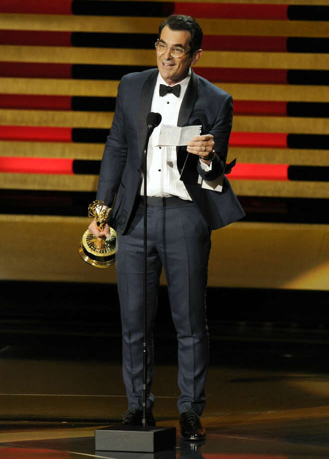 """Ty Burrell accepts the award for outstanding supporting actor in a comedy series for his role in """"Modern Family"""" at the 66th Annual Primetime Emmy Awards at the Nokia Theatre L.A. Live on Monday, Aug. 25, 2014, in Los Angeles. (Photo by Chris Pizzello/Invision/AP)"""