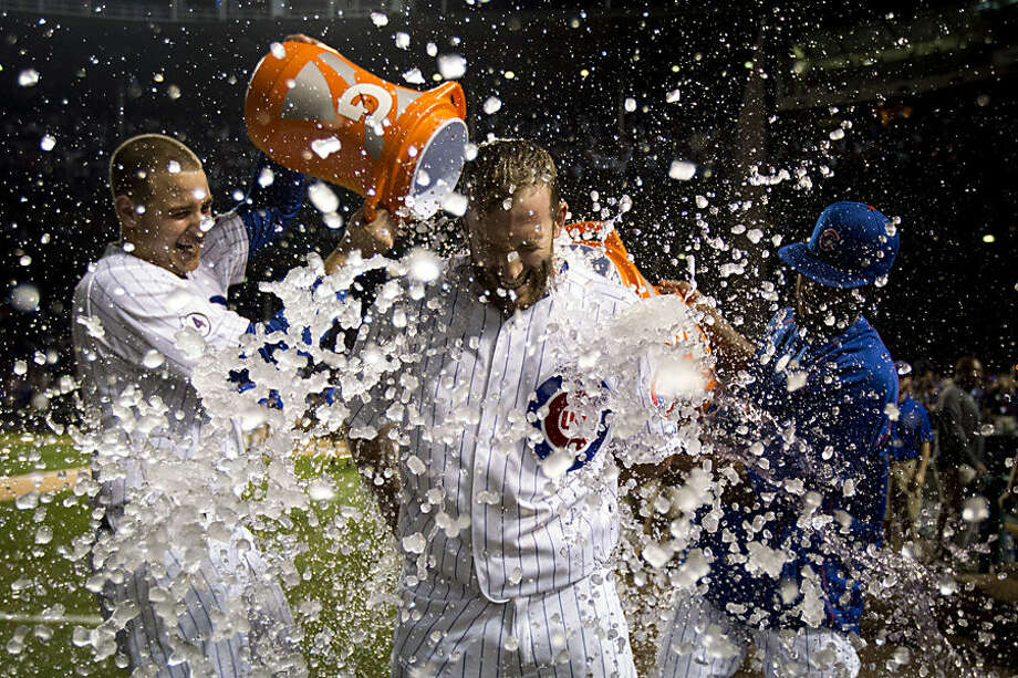 Chicago Cubs Chris Denorfia has water dumped on him by teammates Anthony Rizzo, left, and Dexter Fowler, right, after a walk-off home run against the Kansas City Royals during the 11th inning of a baseball game Monday, Sept. 28, 2015, in Chicago. The Cubs won 1-0 in 11 innings. (AP Photo/Andrew A. Nelles)