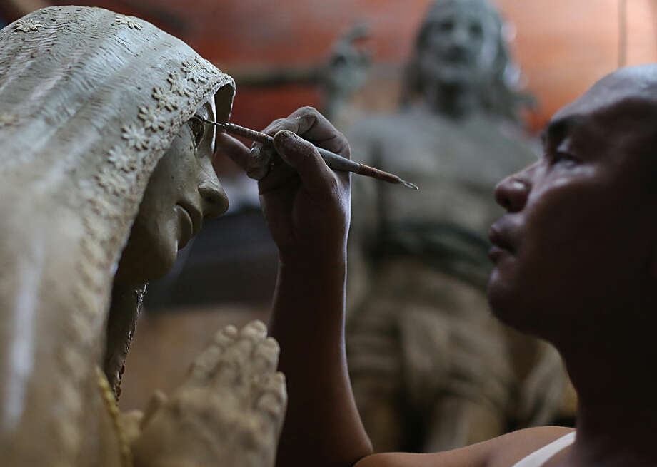Filipino sculptor Frederic Caedo concentrates as he works on an image of the Virgin Mary at his workshop in suburban Quezon city, north of Manila, Philippines on Tuesday, Sept. 29, 2015. Religious images are popular in the Philippines, Asia's largest Roman Catholic nation. (AP Photo/Aaron Favila)