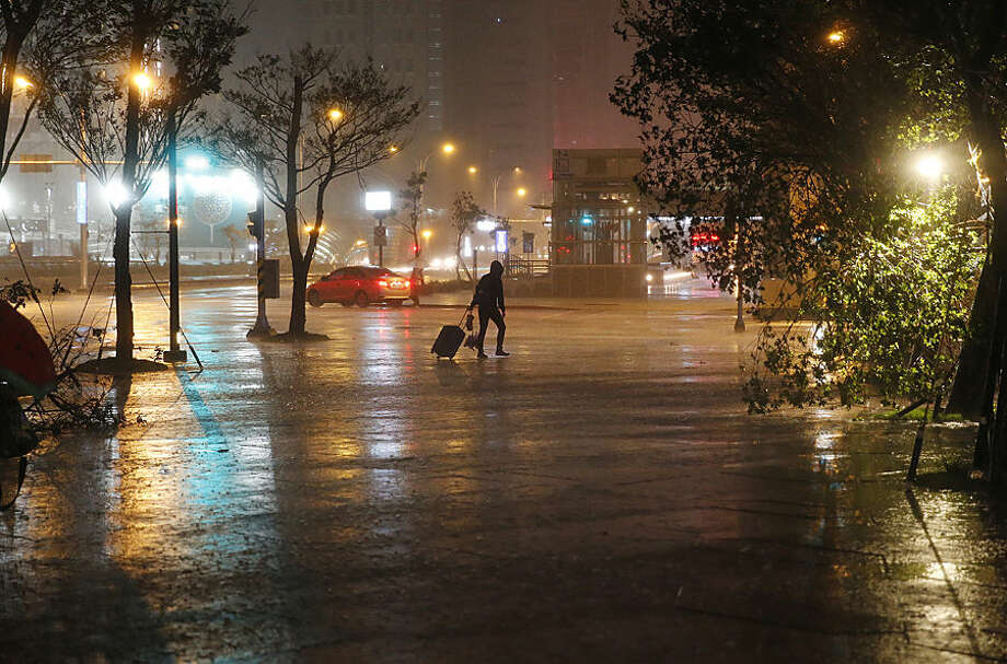 A pedestrian struggles with luggage in the strong winds and rain from Typhoon Dujuan in the business district of Taipei, Taiwan, Monday, Sept. 28, 2015. Dujuan picked up strength Sunday as it approached Taiwan, prompting warnings of strong winds and torrential rain. (AP Photo/Wally Santana)