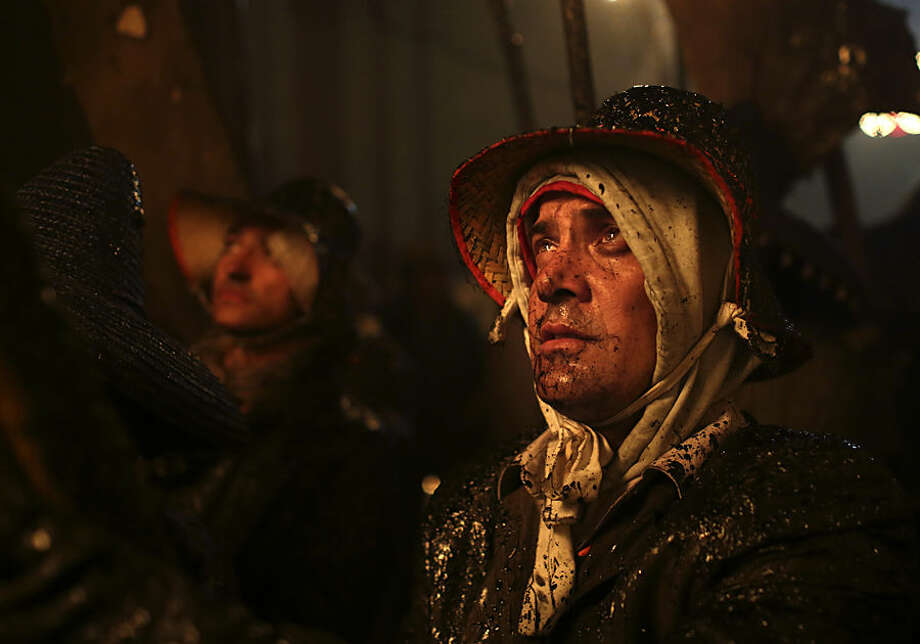 A villager dressed up in old clothes and wearing a hat takes part in The Civic procession of el Vitor in the town of Mayorga in Valladolid, Spain, Monday, Sept. 28, 2015. Villagers from a small village in the northern Spain burn leather wineskins that are hung from poles and between the songs of worshipers, the cloud of smoke, the fire and the smell of burnt fish pays homage to Santo Toribio, a missionary native to the village of Mayorga who was canonised in the 18th century. These acts of devotion are held in memory of the day that the villagers received the remains of the saint, in whose name the people went into the streets with flaming torches and lanterns. (AP Photo/Jose Vicente)