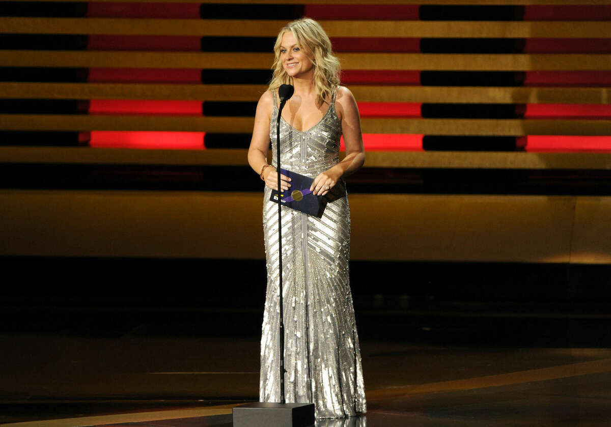 Amy Poehler presents the award for outstanding supporting actor in a comedy series on stage at the 66th Annual Primetime Emmy Awards at the Nokia Theatre L.A. Live on Monday, Aug. 25, 2014, in Los Angeles. (Photo by Chris Pizzello/Invision/AP)