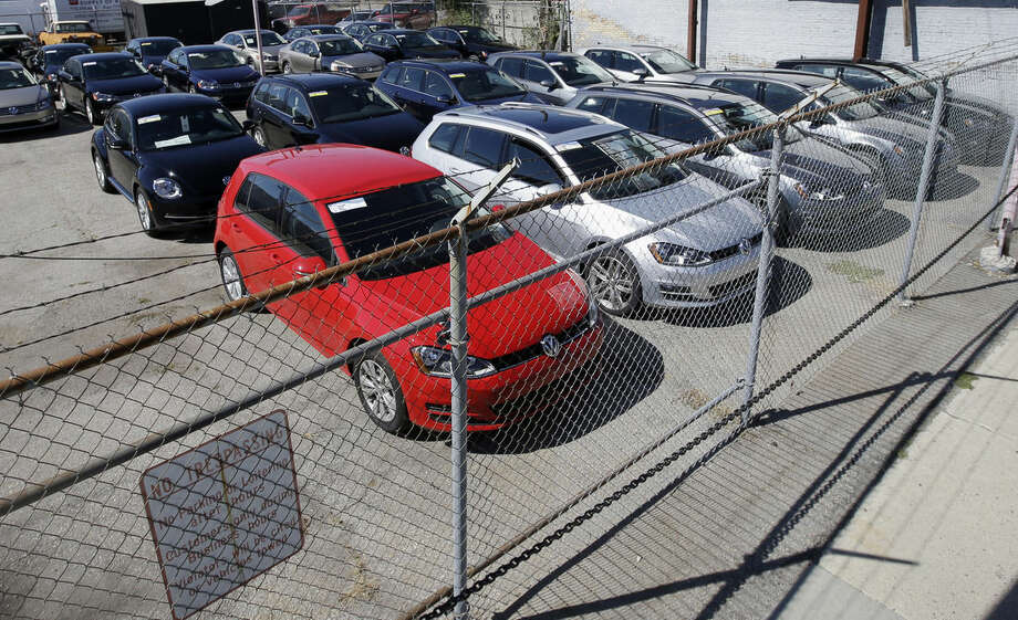 "FILE - In this Sept. 23, 2015 file photo, diesel Volkswagens are seen behind a security fence on a storage lot near a VW dealership in Salt Lake City. Volkswagen is far from the first company to stand accused of trying to game required emissions tests. Almost since the passage of the Clean Air Act in 1970, major manufacturers of cars, trucks and heavy equipment have been busted for using what regulators call ""defeat devices"" _ typically programing a vehicle's on-board computer to boost horsepower or fuel mileage by belching out dirtier exhaust than allowed. (AP Photo/Rick Bowmer, File)"