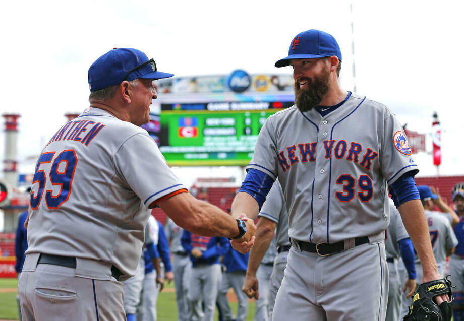New York Mets pitching coach Dan Warthen shakes hands with relief pitcher Bobby Parnell after defeating the Cincinnati Reds 8-1, in a baseball game, Sunday, Sept. 27, 2015, in Cincinnati. The Mets won 8-1. (AP Photo/Aaron Doster)