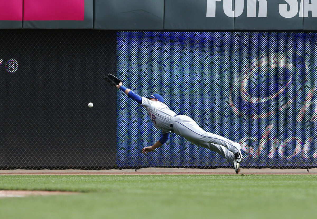 New York Mets left fielder Michael Conforto (30) is unable to make a catch on a ball hit by Cincinnati Reds Skip Schumaker in the first inning of a baseball game, Sunday, Sept. 27, 2015, in Cincinnati. The Mets won 8-1. (AP Photo/Aaron Doster)