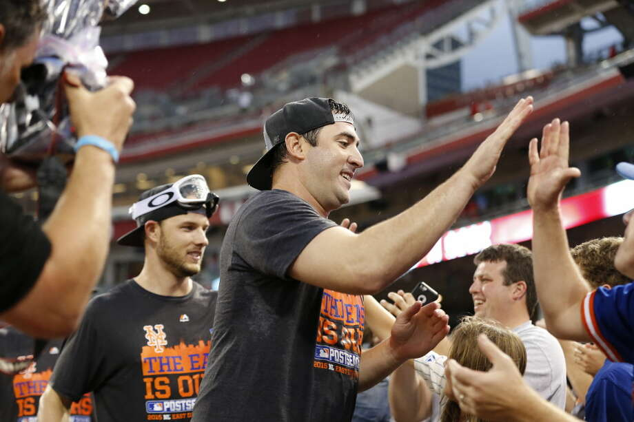 OUT OF CAMERA FILE - New York Mets' Matt Harvey celebrates with the fans after the clinching the NL East title following their 10-2 win over the Cincinnati Reds, Saturday, Sept. 26, 2015, in Cincinnati. (AP Photo/Aaron Doster)