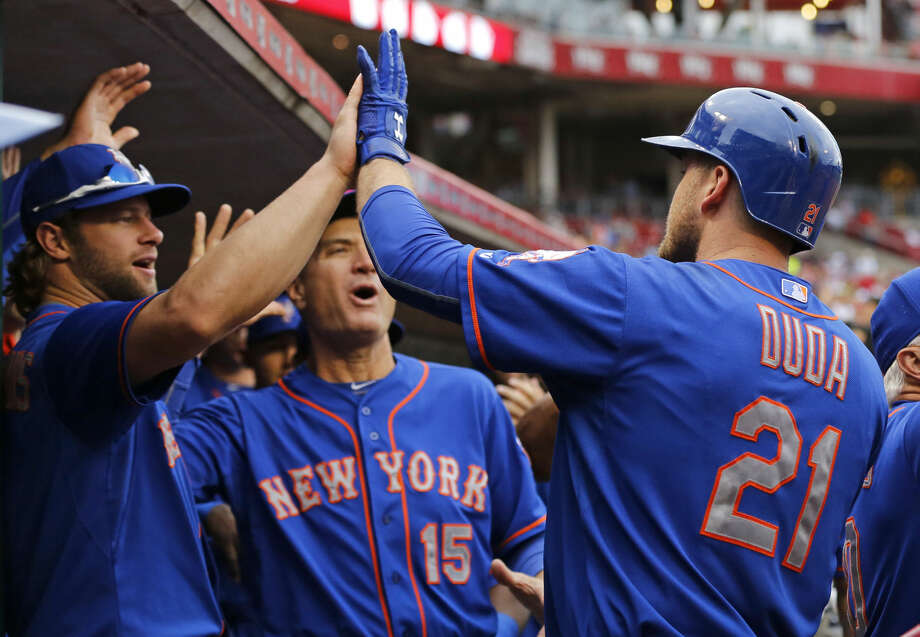 New York Mets first baseman Lucas Duda (21) celebrates with teammates in the dugout after hitting a grand slam in the first inning of a baseball game against the Cincinnati Reds, Saturday, Sept. 26, 2015, in Cincinnati. The Mets won 10-2. (AP Photo/Aaron Doster)