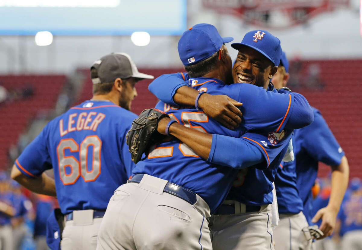 New York Mets right fielder Curtis Granderson (right) hugs bullpen coach Ricky Bones (25) after clinching the NL East title following their 10-2 win over the Cincinnati Reds, Saturday, Sept. 26, 2015, in Cincinnati. (AP Photo/Aaron Doster)