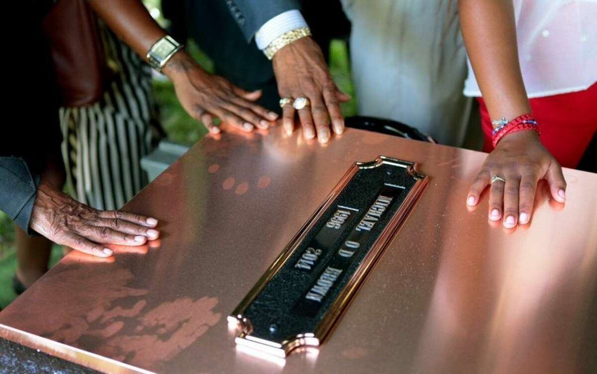 Family members touch the copper top of the vault containing the casket of Michael Brown during his funeral on Monday, Aug. 25, 2014, in Normandy, Mo. Hundreds of people gathered to say goodbye to Brown, who was shot and killed by a Ferguson, Mo., police officer on Aug. 9. (AP Photo/St. Louis Post Dispatch, Robert Cohen, Pool)