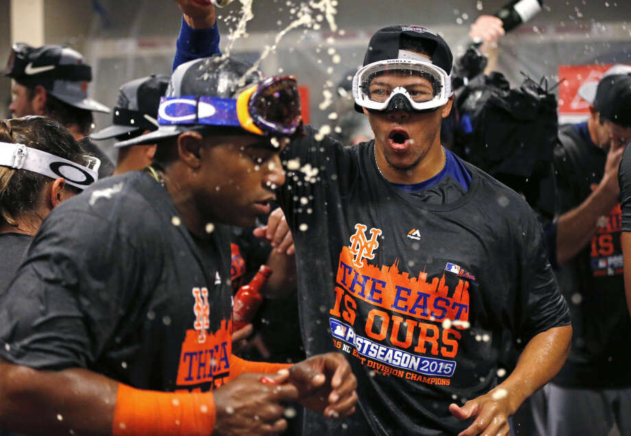 The New York Mets celebrate in the clubhouse after clinching the NL East with a 10-2 win over the Cincinnati Reds in a baseball game, Saturday, Sept. 26, 2015, in Cincinnati. (AP Photo/Aaron Doster)