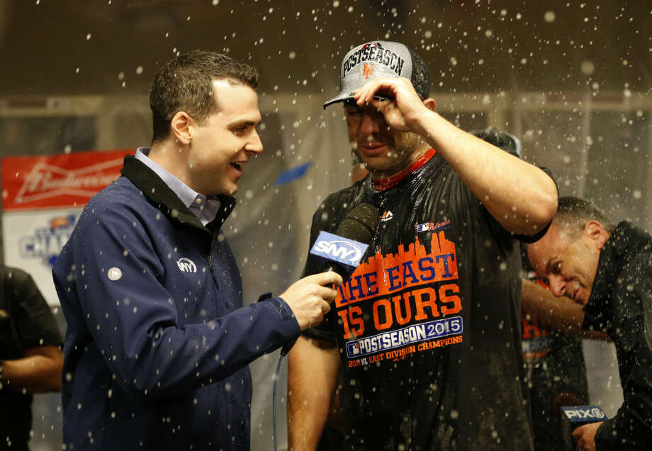 New York Mets' David Wright is interviewed in the clubhouse as they celebrate in the clubhouse after the clinching the NL East title following their 10-2 win over the Cincinnati Reds in a baseball game, Saturday, Sept. 26, 2015, in Cincinnati. (AP Photo/Aaron Doster)