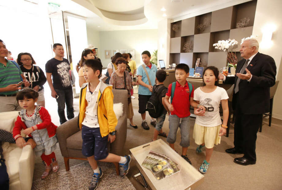 In this July 18, 2014 photo, South Coast Plaza General Manager Werner Escher, right, welcomes Chinese tourists visiting the shopping center into the VIP room in Costa Mesa, Calif. Chinese tourism is surging and the mall is a popular destination that is doing what it can to keep the buses coming, from accepting China's UnionPay card to providing Mandarin-speaking salespeople. Tourism from China to the United States has soared since the countries signed an agreement in 2007 promoting travel. (AP Photo/Damian Dovarganes)