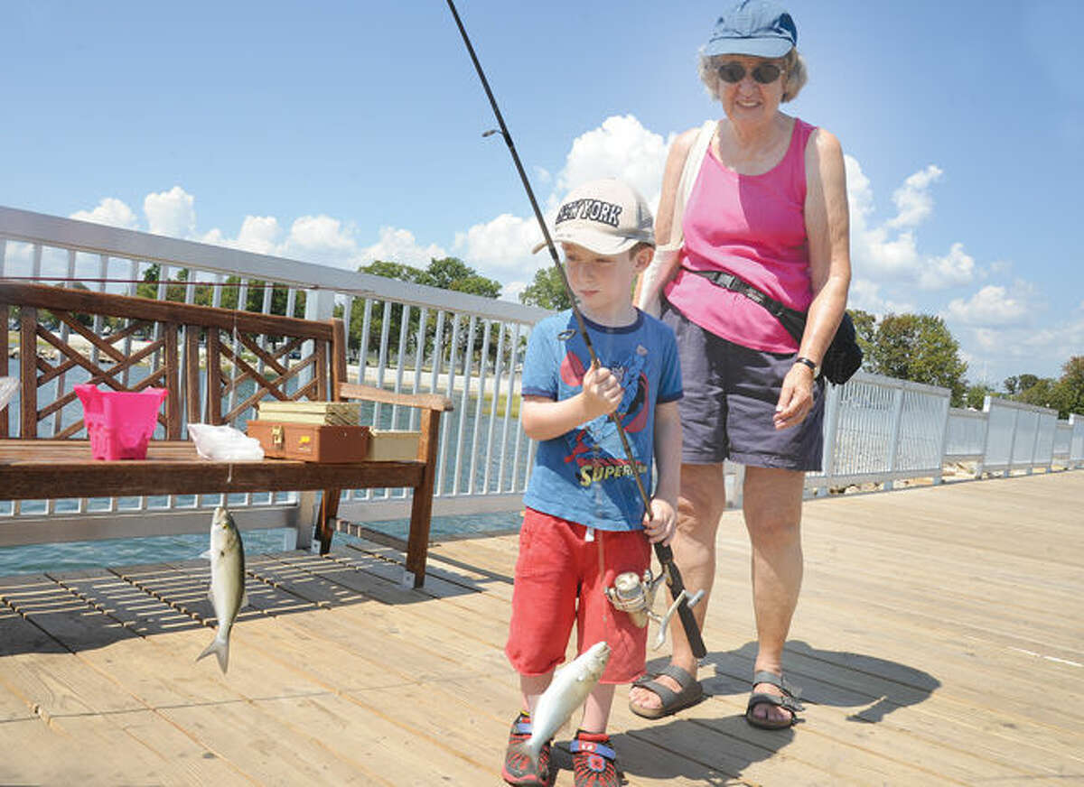 David Kossar 4, pulls in some fish with his grandmother Nancy Kossar Tuesday afternoon on the pier at Calf Pasture Beach. Hour photo/Matthew Vinci