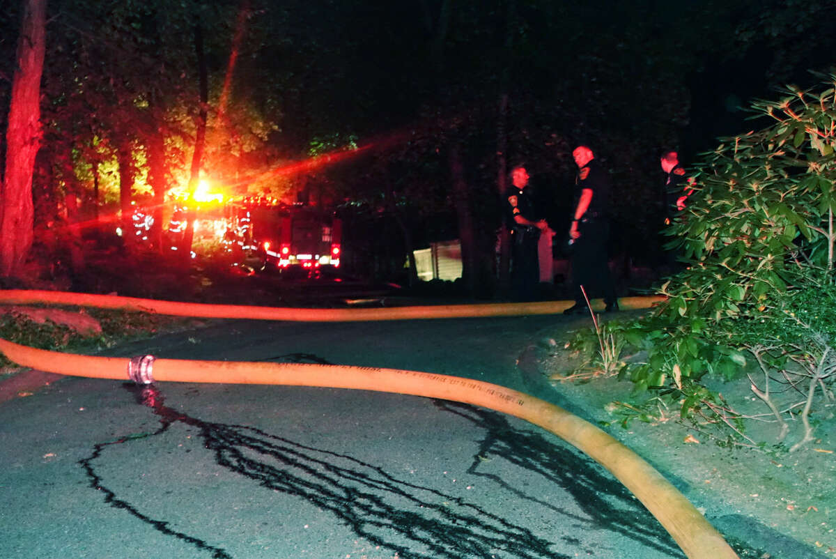 Hour photo/Chris Bosak Norwalk police respond to a fully involved structure fire at 56 Witch Lane Thursday night.