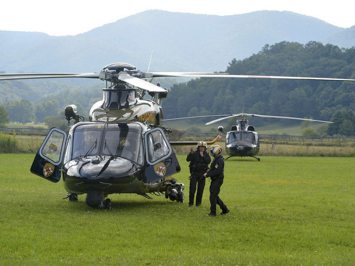 The flight crew for a Maryland State Police helicopter prepares to take off from the mobile command center in Deerfield, Va., on Wednesday, Aug. 27, 2014. The helicopter is one of several being used in a search and rescue mission to locate the missing pilot of an F15c fighter jet which crashed into a mountain near Elliot Knob in Augusta County. (AP photo/The News Leader, Mike Tripp)