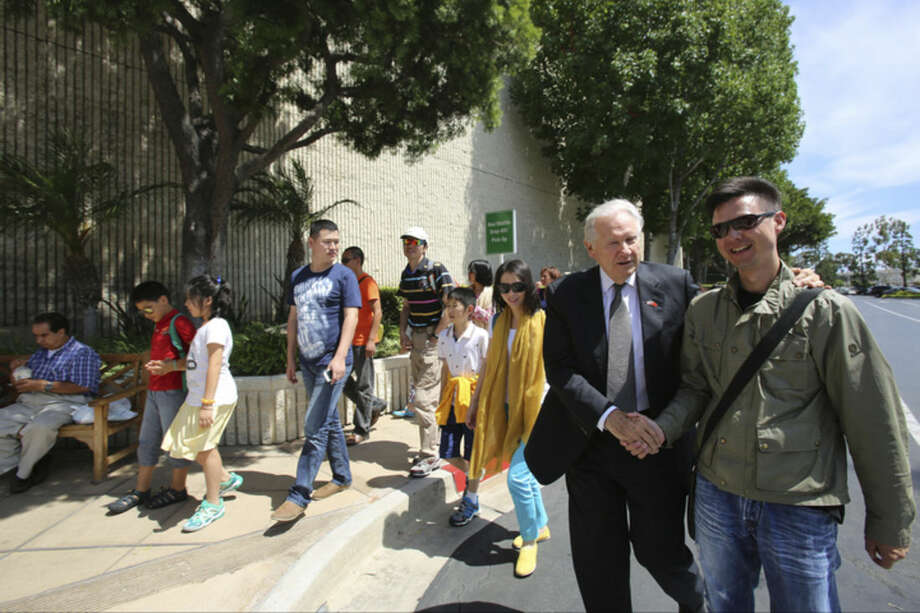 In this July 18, 2014 photo, South Coast Plaza General Manager Werner Escher, second from right, greets Chinese tourists visiting the shopping center in Costa Mesa, Calif. Chinese tourism is surging and the mall is a popular destination that is doing what it can to keep the buses coming, from accepting China's UnionPay card to providing Mandarin-speaking salespeople. Tourism from China to the United States has soared since the countries signed an agreement in 2007 promoting travel. (AP Photo/Damian Dovarganes)