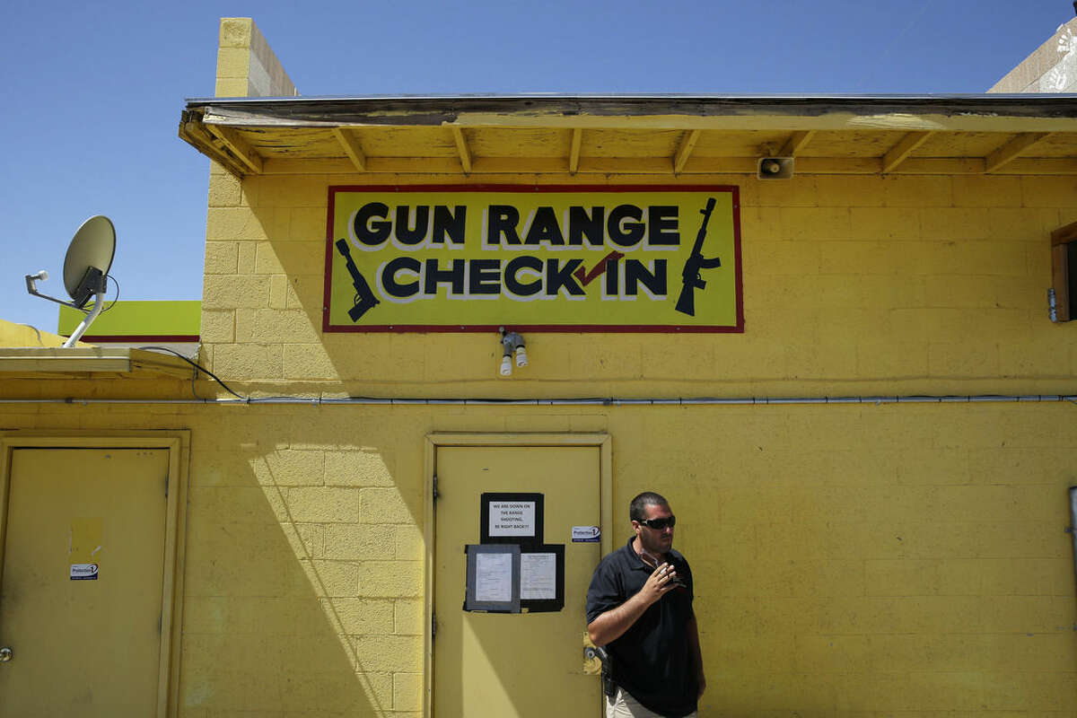 An employee smokes outside of an office for the Last Stop outdoor shooting range Wednesday, Aug. 27, 2014, in White Hills, Ariz. Instructor Charles Vacca was accidentally killed at the range by a 9-year-old with an Uzi submachine gun. (AP Photo/John Locher)
