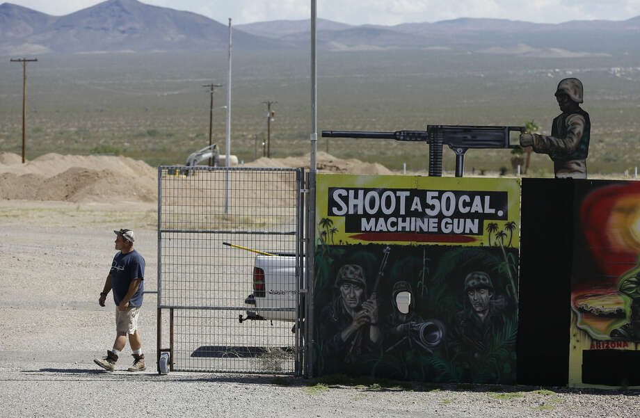 A man closes off an entrance to the Last Stop outdoor shooting range Wednesday, Aug. 27, 2014, in White Hills, Ariz. Gun range instructor Charles Vacca was accidentally killed Monday, Aug. 25, 2014 at the range by a 9-year-old with an Uzi submachine gun. (AP Photo/John Locher)