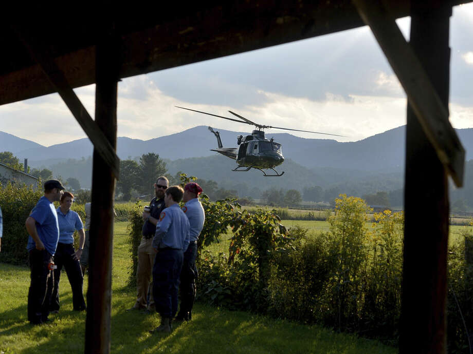 A helicopter takes off near search team members who wait for their turn to join the search for a missing pilot at the mobile command center in Deerfield, Va., on Wednesday, Aug. 27, 2014. The search is for the missing pilot of an F15c fighter jet which crashed into a mountain near Elliot Knob in Augusta County. (AP photo/The News Leader, Mike Tripp)