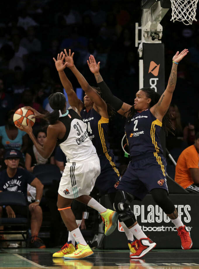 Indiana Fever forward Erlana Larkins (2) and Indiana Fever forward Tamika Catchings (24) defend New York Liberty center Tina Charles (31) during the first half in Game 3 of the WNBA basketball Eastern Conference finals at Madison Square Garden in New York, Tuesday, Sept. 29, 2015. (AP Photo/Adam Hunger)