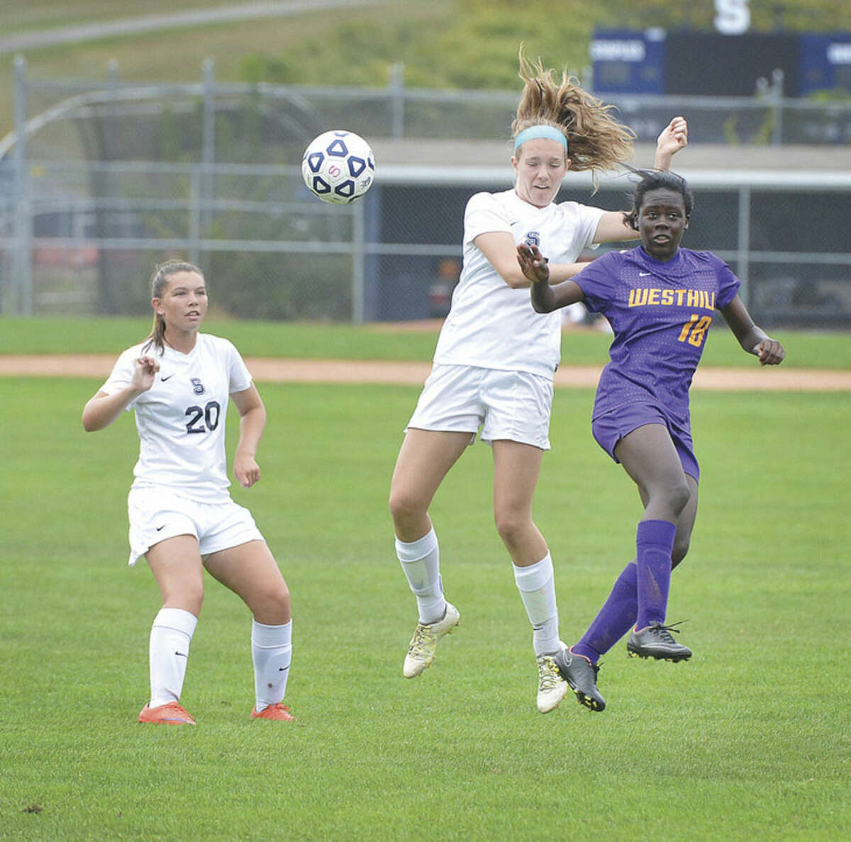 Hour photo/Alex von Kleydorff Staples' Sally McGee, center, battles Westhill's Chelsea Demond, right, for an air ball as the Wreckers' Annie Amacker (20) looks on during Tuesday's FCIAC girls soccer game at Loeffler Field.
