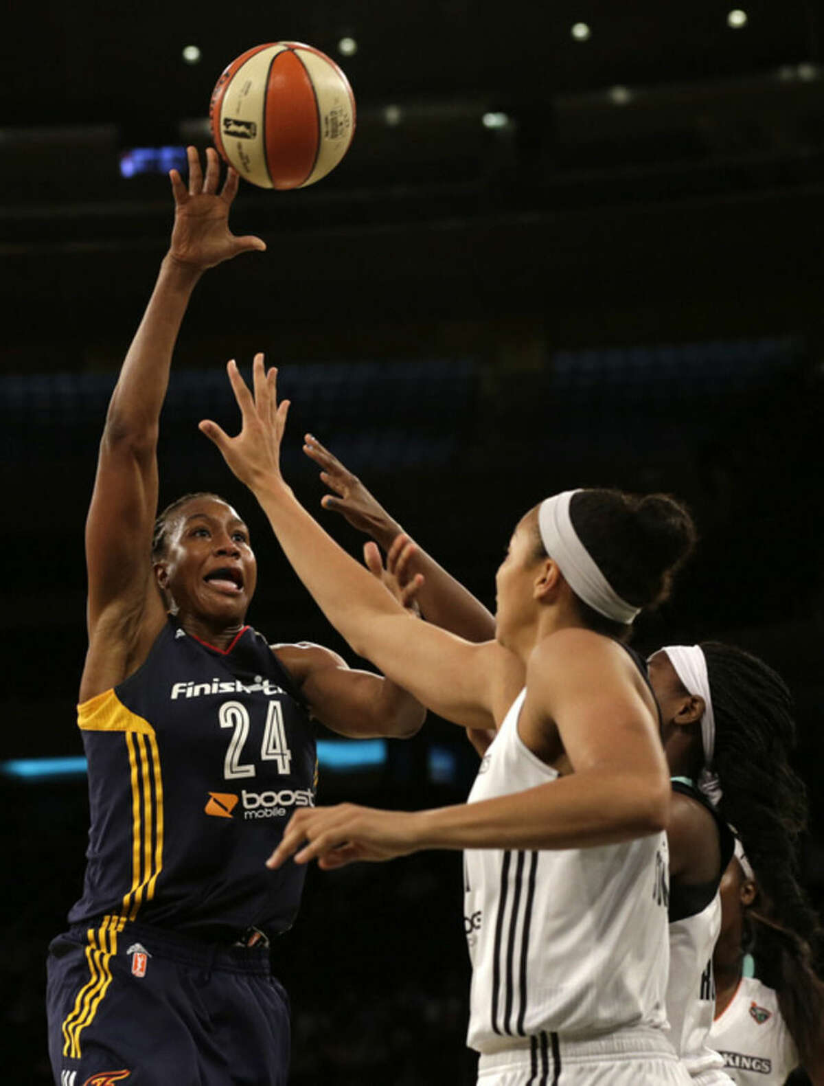 Indiana Fever forward Tamika Catchings, left, shoots over New York Liberty center Kiah Stokes, right, during the first half in Game 3 of the WNBA basketball Eastern Conference finals at Madison Square Garden in New York, Tuesday, Sept. 29, 2015. (AP Photo/Adam Hunger)