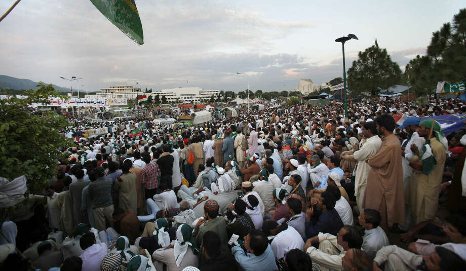 Thousands of supporters of Pakistani Muslim cleric Tahir-ul-Qadri listen to their leader during a sit-in protest near the parliament building, seen in background, in Islamabad, Pakistan, Thursday, Aug. 28, 2014. Pakistani police have registered a murder case against Prime Minister Nawaz Sharif, his brother Shahbaz, key cabinet members and senior officials on charges of abetting 14 murders of the supporters of a fiery cleric who has been leading for two weeks thousands of anti-government protests in capital Islamabad. (AP Photo/Anjum Naveed)