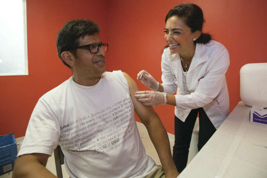 Luis Quiroz Llomtop gets his flu shot by Walgreens Pharmacist Angela Nikitas at the Norwalk Community Center Saturday afternoon.