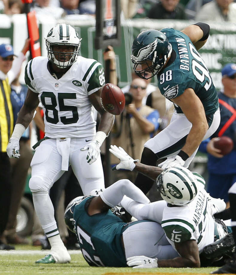 New York Jets wide receiver Brandon Marshall (15) makes a lateral pass into Philadelphia Eagles outside linebacker Connor Barwin (98) as he is tackled by Philadelphia Eagles free safety Malcolm Jenkins (27) during the second quarter of an NFL football game, Sunday, Sept. 27, 2015, in East Rutherford, N.J. The Eagles recovered the ball on the play as the pass was ruled a fumble. (AP Photo/Adam Hunger)