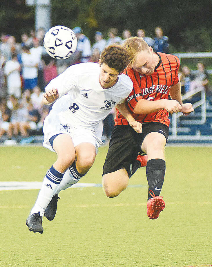 Hour photo/John Nash - Jordan Lord, left, heads the ball against Ridgefield Tigers player Edwin Hassenstein during Monday's FCIAC boys soccer game in Wilton.