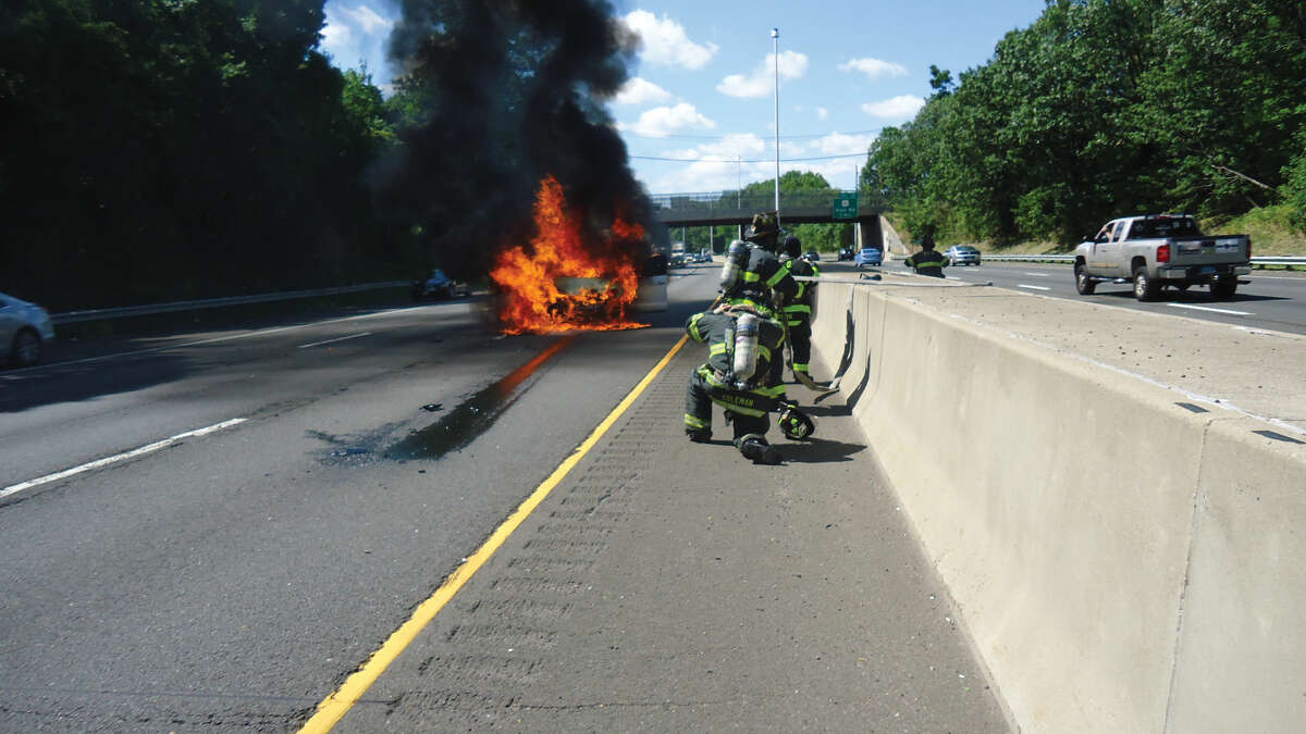 Contributed photo Norwalk Firefighters respond to a fully involved car fire on I-95 Thursday afternoon.