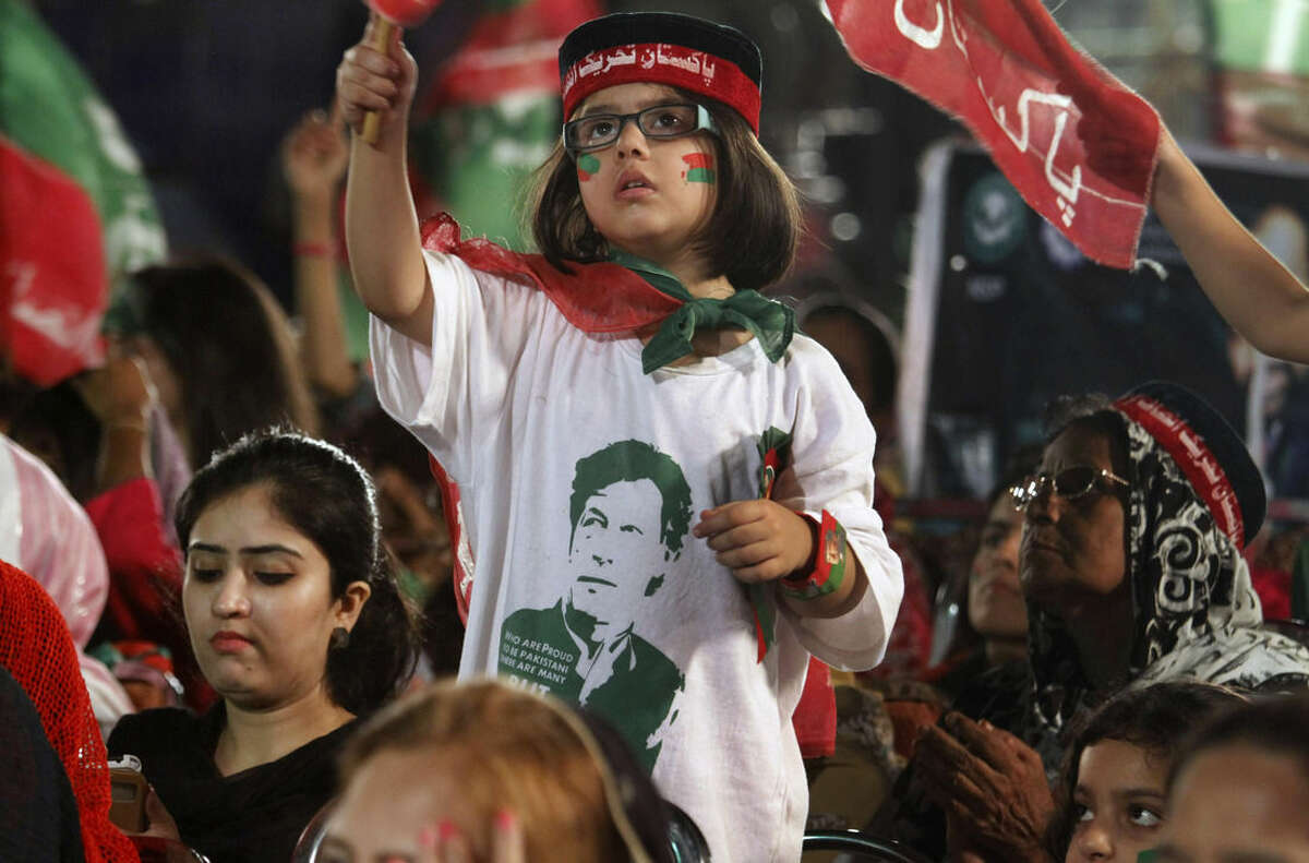 A girl wears a shirt with the picture of Pakistan's cricketer-turned-politician Imran Khan as she takes part in a protest near the parliament building in Islamabad, Pakistan, Thursday, Aug. 28, 2014. Pakistani police have registered a murder case against Prime Minister Nawaz Sharif, his brother Shahbaz, key cabinet members and senior officials on charges of abetting 14 murders of the supporters of a fiery cleric who has been leading for two weeks thousands of anti-government protests in capital Islamabad. (AP Photo/Anjum Naveed)