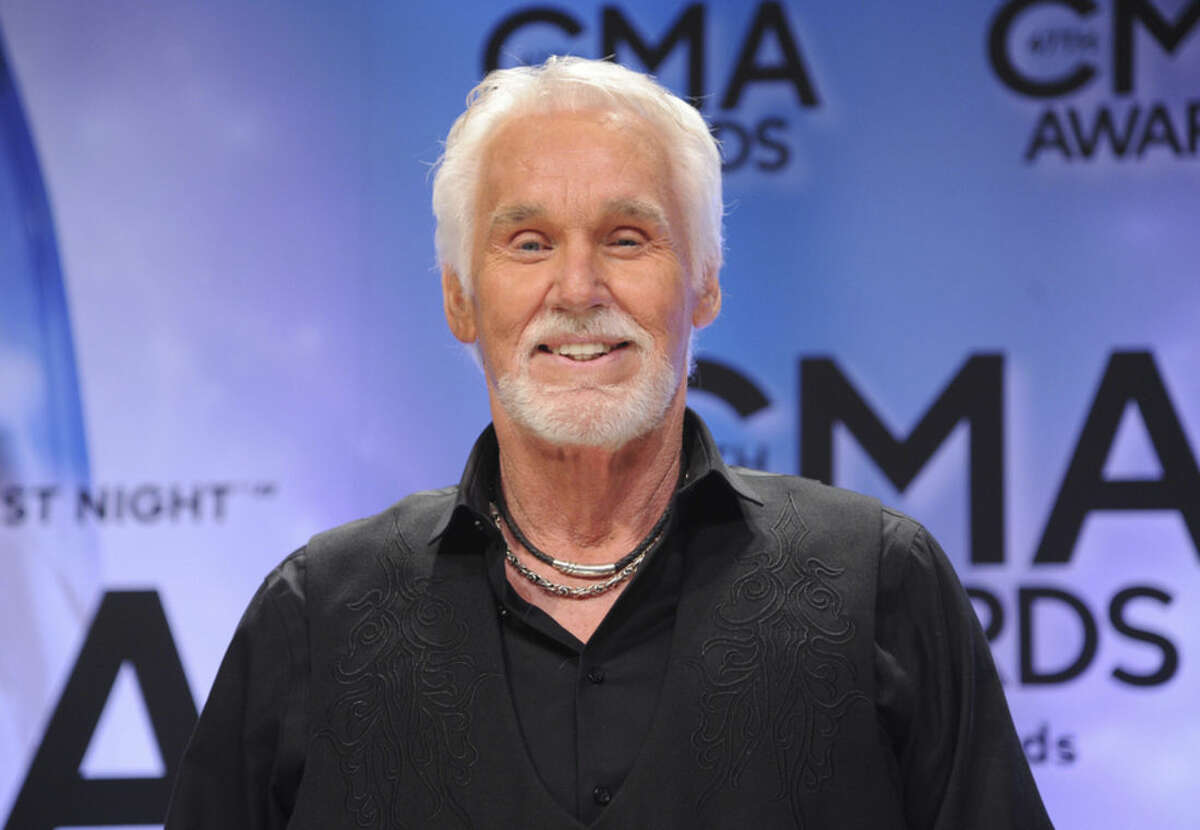 FILE - In this Nov. 6, 2013 file photo, Kenny Rogers, winner of the Willie Nelson lifetime achievement award, poses backstage at the 47th annual CMA Awards in Nashville, Tenn. Rogers said he is retiring from touring and will do one last worldwide farewell tour after five decades on the road. Rogers, 77, said in a video message on his website that he wants to spend more time with his two young sons and his wife, Wanda. (Photo by Evan Agostini/Invision/AP, File)