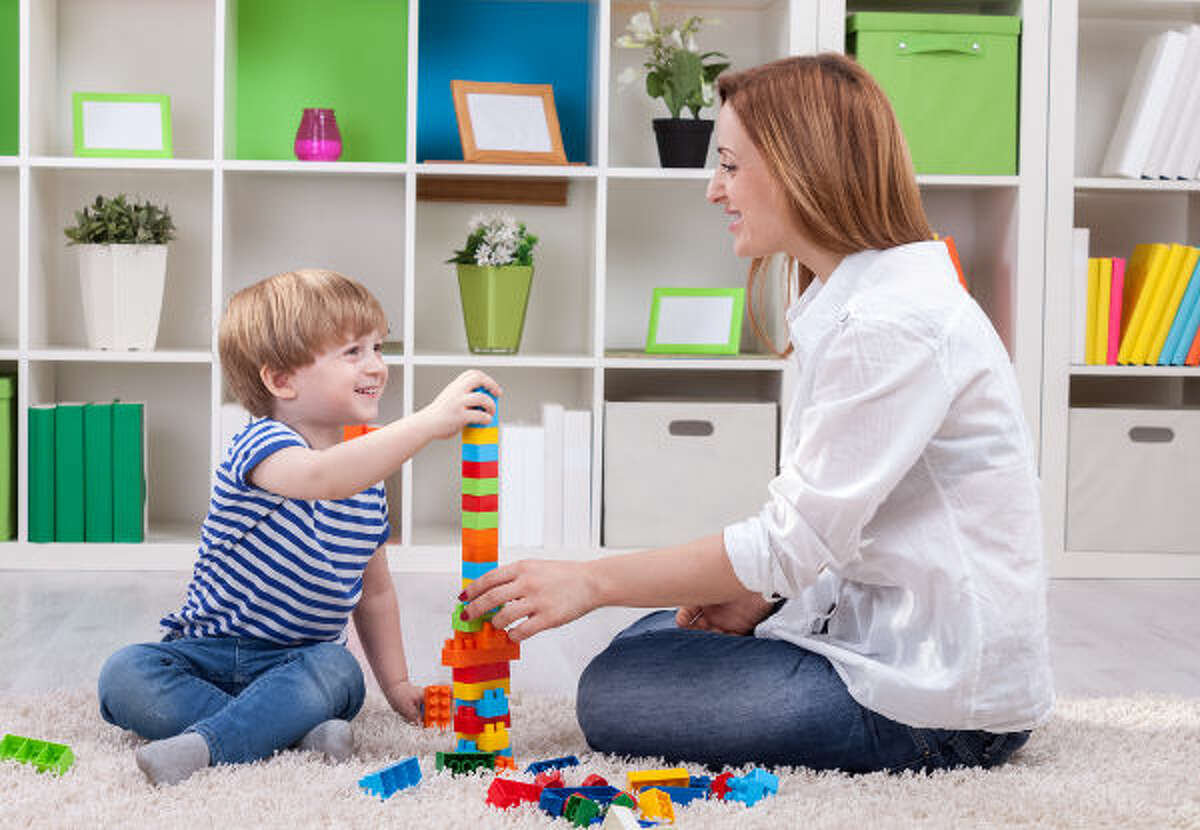 Mother and child build toy tower succes