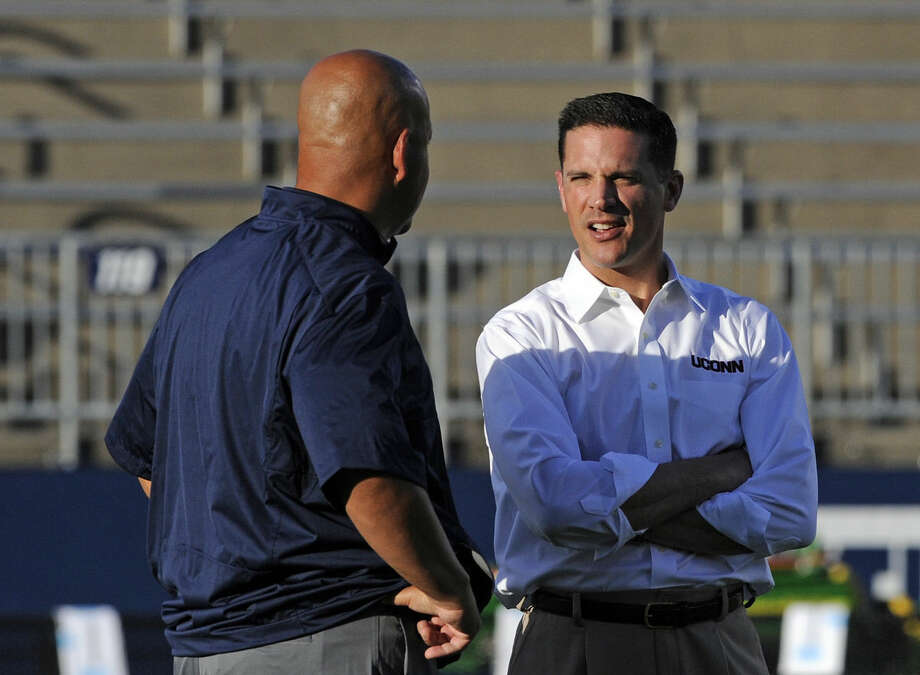 Connecticut head coach Bob Diaco speaks with BYU receiver coach Guy Holliday before the first half of their NCAA football game in East Hartford, Conn., on Friday, Aug. 29, 2014. (AP Photo/Fred Beckham)