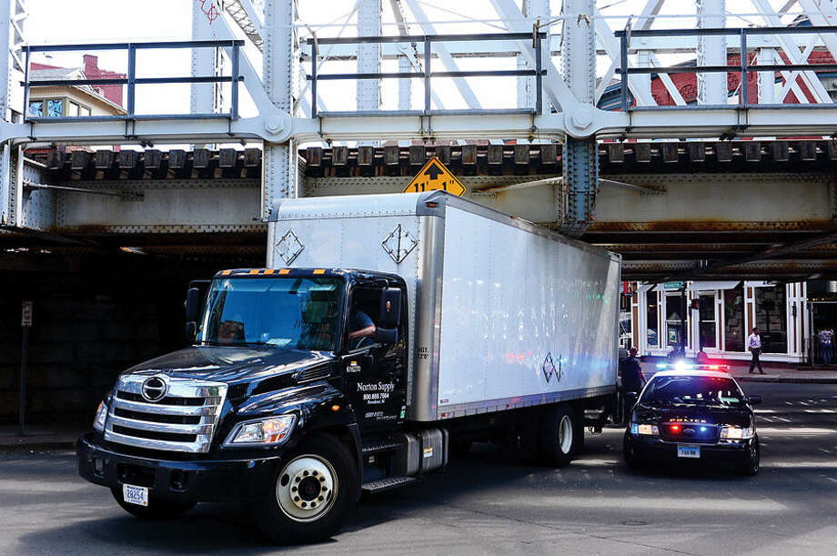 Hour photo / Erik Trautmann A Norton Supply truck became stuck underneath the Washington St train bridge disrupting Metro North service Thursday.