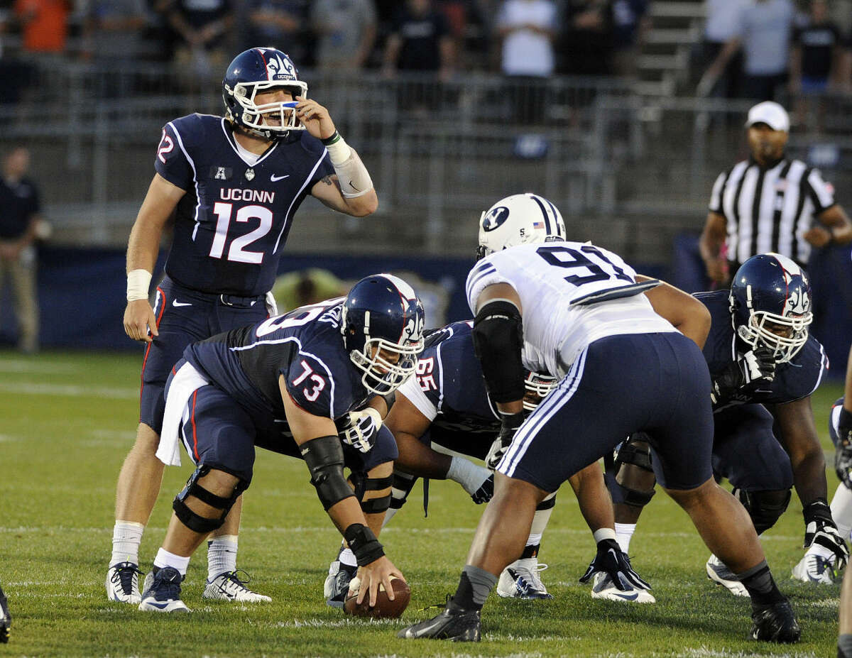 Connecticut quarterback Casey Cochran (12) calls out a play during the first half of an NCAA college football game against BYU in East Hartford, Conn., Friday, Aug. 29, 2014. (AP Photo/Fred Beckham)