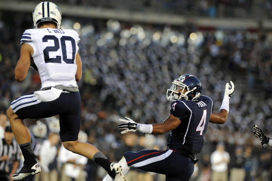 Connecticut wide receiver Deshon Foxx (4) watches as a pass intended for him is intercepted by BYU defensive back Craig Bills (20) during the first half of an NCAA college football game in East Hartford, Conn., Friday, Aug. 29, 2014. (AP Photo/Fred Beckham)
