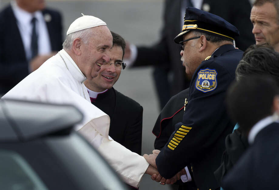 Pope Francis is greeted as he arrives at Philadelphia International Airport in Philadelphia, Saturday, Sept. 26, 2015. The Pope will spend the last two of his six days in the U.S. in Philadelphia as the star attraction at the World Meeting of Families, a conference for more than 18,000 people from around the world that has been underway as the pope traveled to Washington and New York. (AP Photo/Susan Walsh)