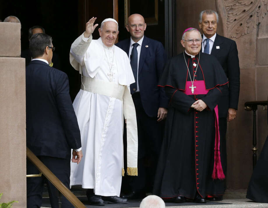 Pope Francis waves as Archbishop Charles Chaput, right, stands by, prior to celebrating Mass Saturday, Sept. 26, 2015, at the at the Cathedral Basilica of Sts. Peter and Paul in Philadelphia. (AP Photo/Patrick Semansky)