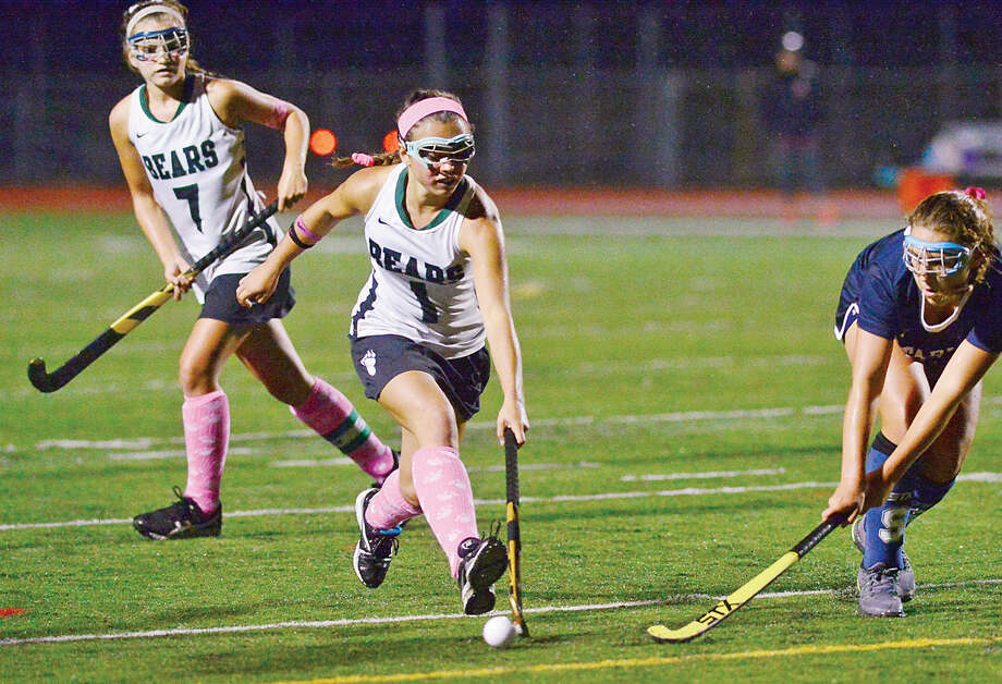 Hour photo / Erik Trautmann Norwalk High School Field Hockey player Grace Bradley gets her stick on the ball as captain Sarah Roddy back her up during their game against Staples Thursday night.