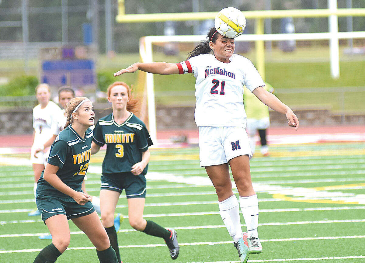 Hour photo/John Nash - Brien McMahon's Olivia Rosado, right, heads the ball away from Trinity Catholic players Stephanie Bragg, leeft, and Lily Shanahan (3) during Wednesday's FCIAC girls soccer game at Casagrande Field in Norwalk.