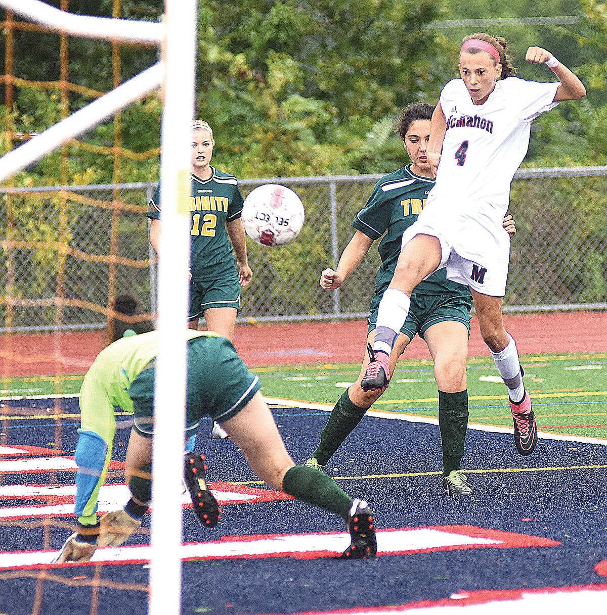 Hour photo/John Nash - Brien McMahon freshman Chloe Ortolano (4) blasts a goal into the net during Wednesday's FCIAC girls soccer game against Trinity Catholic.