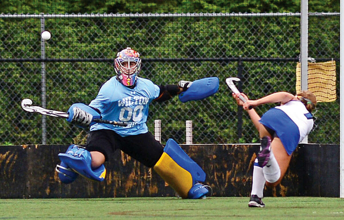 Hour photo / Erik Trautmann Goalie for Wilton high School Girls Field Hockey team Amanda Hendry tries to ward off a goal during their game against Darien Thursday.