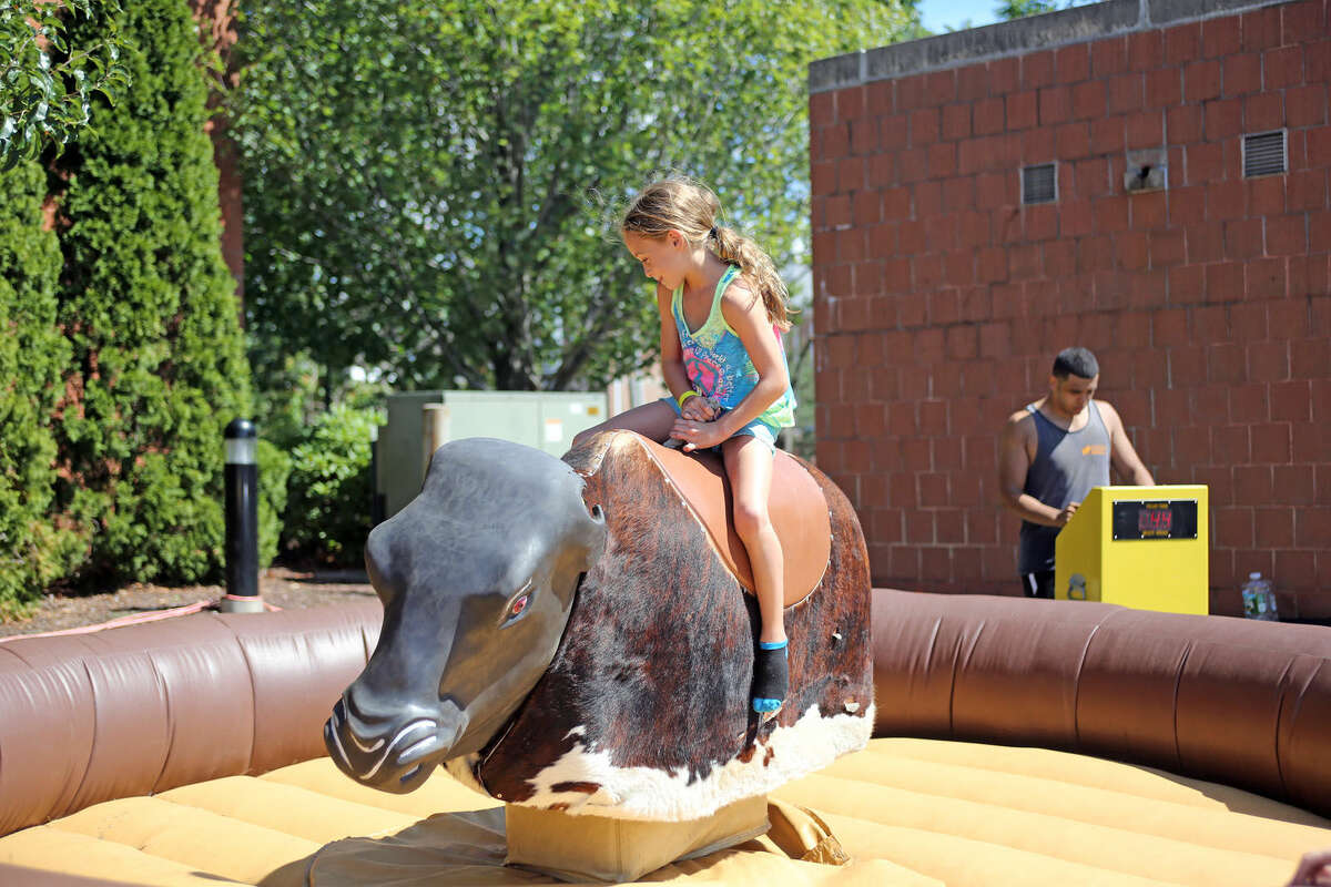 Esther Bernstein, 7, rides a mechanical bull during the 7th Annual Blues, Views & BBQ Festival Saturday at Levitt Pavilion and the Westport Library. Hour Photo / Danielle Calloway