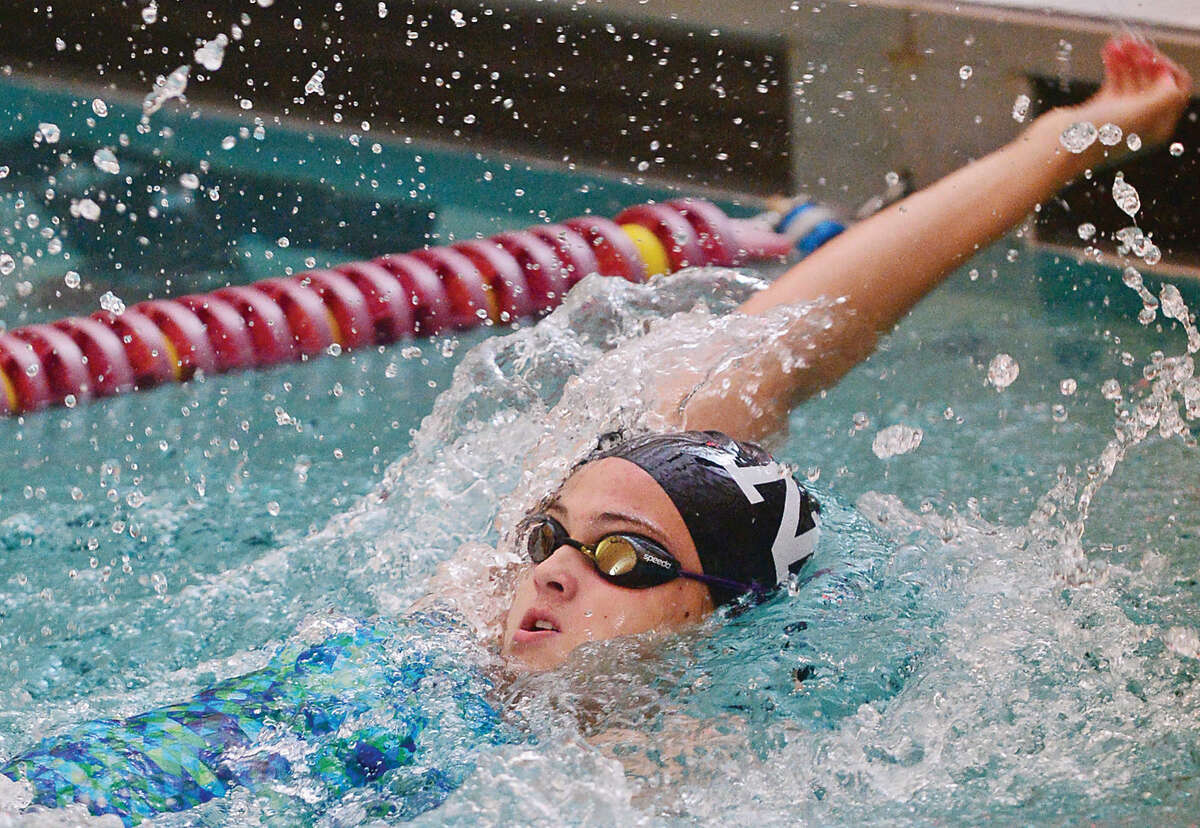 Hour photo / Erik Trautmann Isabel Anbar competes in the 200 backstroke in their swim meet against Wilton at the Wilton YMCA Wednesday.