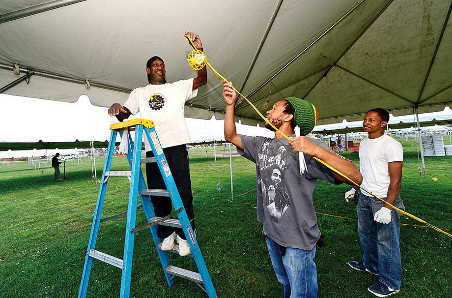Hour photo / Erik Trautmann Troy Mikel, Jah Barnabas and Sheldon Frierson string lights at Veteran's Memorial Park Friady in preparation for next weeknds Norwalk Seaport Association Oyster Festival.
