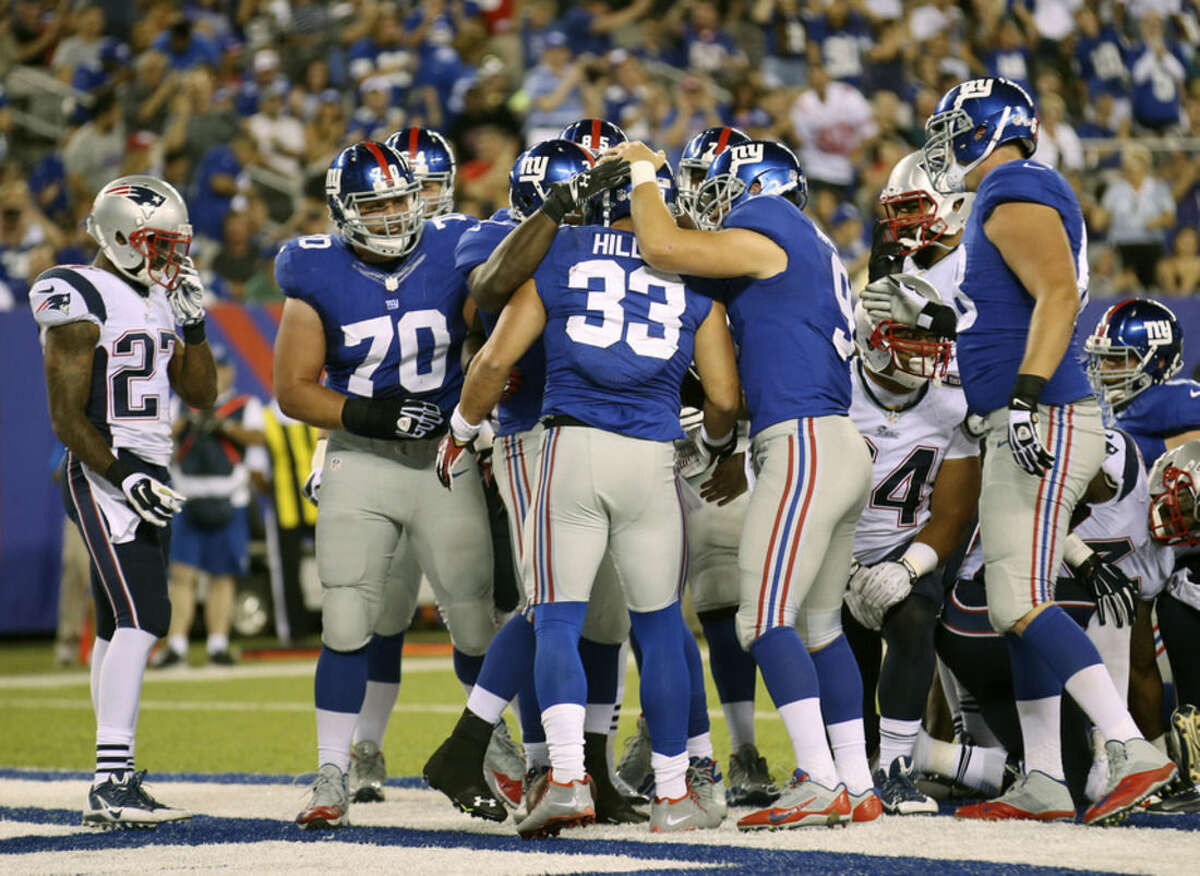 Teammates congratulate New York Giants' Peyton Hillis (33), center, after he scored a touchdown during the first half of an NFL preseason football game against the New England Patriots, Thursday, Aug. 28, 2014, in East Rutherford, N.J. (AP Photo/John Minchillo)
