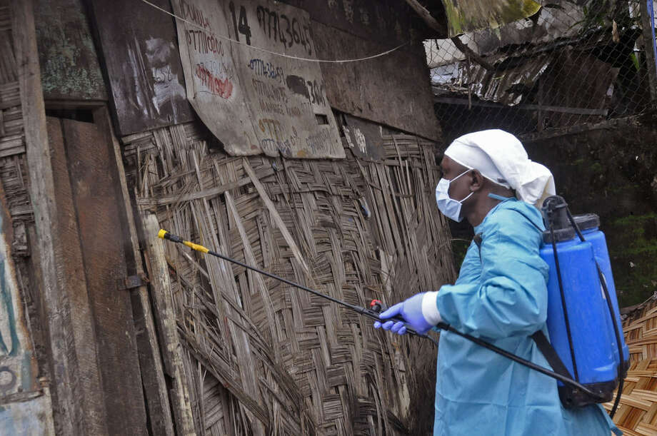 A Liberian health worker spray disinfectant outside a house before entering and removing the body of a man that they believe died from the Ebola virus in Monrovia, Liberia, Friday, Aug. 29, 2014. The Ebola outbreak in West Africa eventually could exceed 20,000 cases, more than six times as many as are now known, the World Health Organization said Thursday. A new plan released by the U.N. health agency to stop Ebola also assumes that the actual number of cases in many hard-hit areas may be two to four times higher than currently reported.(AP Photo/Abbas Dulleh)